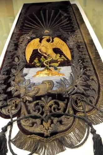 """总统椅背后悬挂的旗帜,上有""""神鹰衔蛇""""图案(金丝线绣、金丝绒)"""