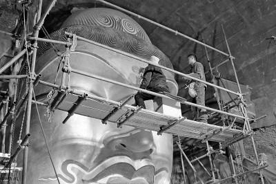 文物修复师李云鹤(左)在进行文物修复。光明图片