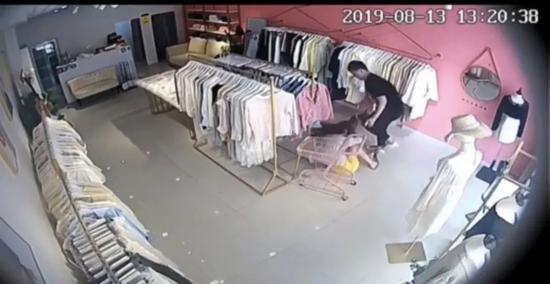 ▲杨宁试图拉开店门逃走,被丈夫拉回摔在地上。视频截图
