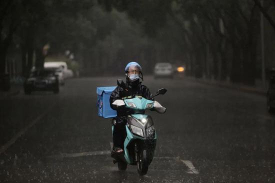外卖员冒雨送餐。新京报记者 郑新洽 摄