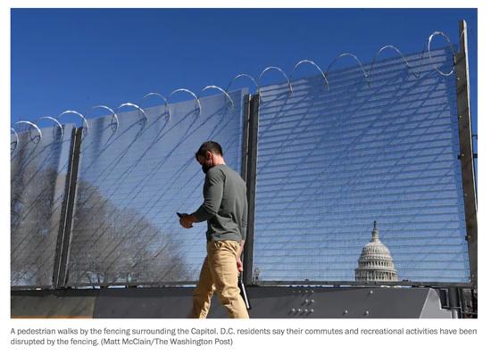 一名行人在国会大厦附近的围栏旁边行走。/《华盛顿邮报》网站截图