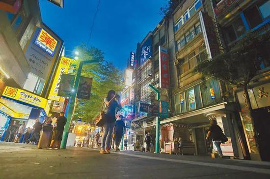 由于全台紧急分区轮流停电,造成台北市西门町内一条街两侧一明一暗,图自台媒
