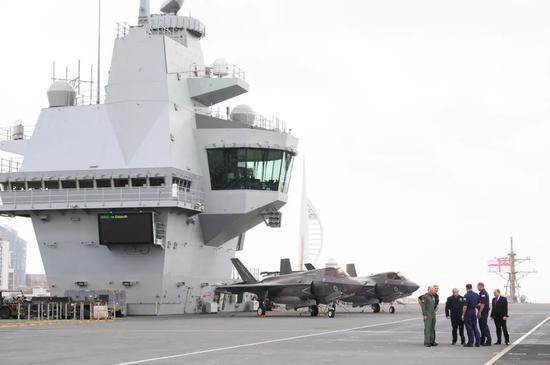 """2021年5月21日,英国首相鲍里斯·约翰逊在""""伊丽莎白女王""""号上与一批武装部队高级官员交谈。来源:路透社"""