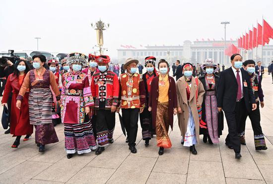 ↑2021年3月5日,十三届全国人大四次会议在北京开幕,全国人大代表走向会场。在十三届全国人大代表中,少数民族代表占代表总数的14%以上,全国55个少数民族都有本民族的代表。