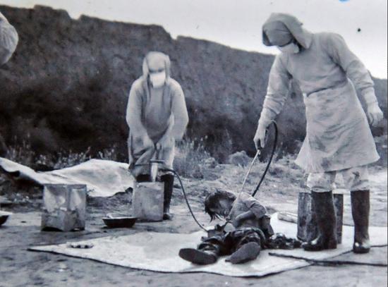 """侵华日军""""731""""部队档案证实,细菌战是日军侵略扩张的重大战略之一。这是翻拍的伪满洲国民生部保健司派员参加1940年11月吉林省农安县鼠疫""""防疫""""活动照片。"""