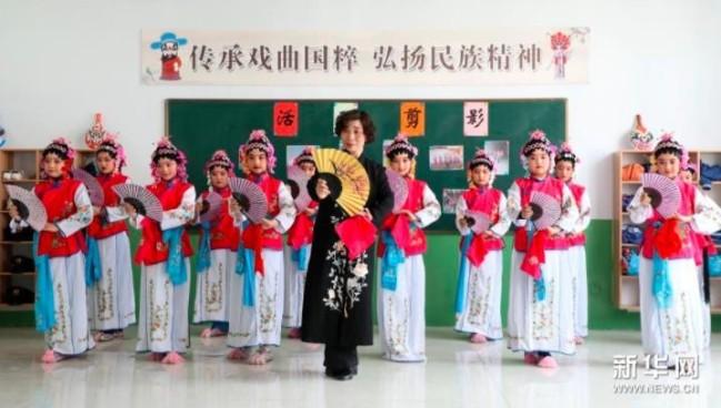 4月12日,在邢台市隆尧县第三实验小学京剧课堂,戏曲老师指导学生练习京剧表演基本功。新华社记者 骆学峰 摄