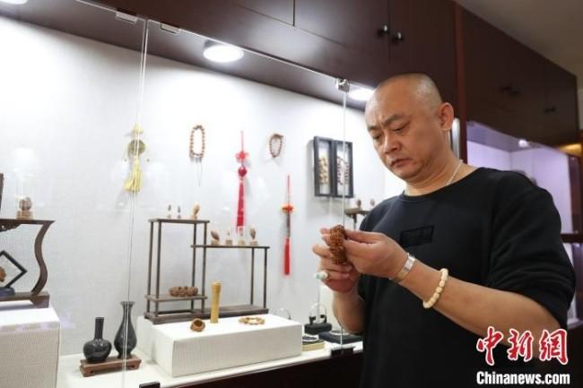 宁夏核雕艺人李文斌正在展示他雕刻好的作品。 于晶 摄