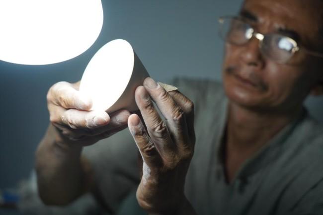 熊国安在查看一只薄胎杯坯(7月14日摄)。新华社记者 周密 摄