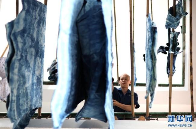 8月10日,在贵州省黔东南苗族侗族自治州丹寨县宁航蜡染工坊,成昊在晾晒浸染好的蜡染时装。 新华社发(黄晓海 摄)