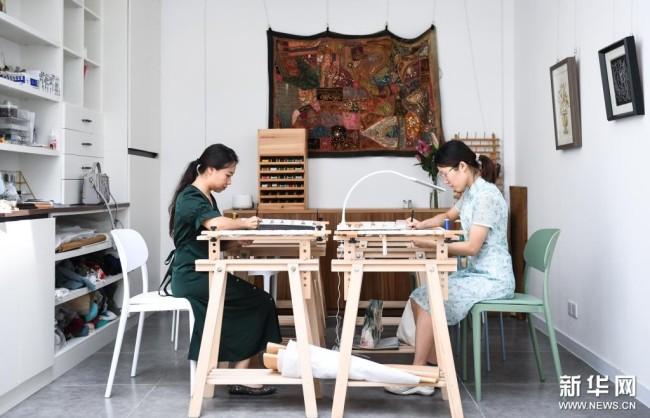 在广州荔湾区泮塘五约的法绣工坊,王颖峰(左)和学员一起刺绣(8月25日摄)。新华社记者 邓华 摄