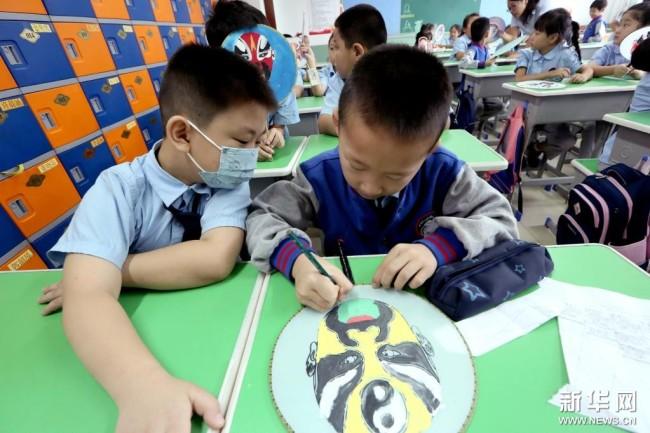 9月6日,在河北省石家庄市栾城区宏远路小学,学生们在绘制扇子脸谱。 新华社发(李明发 摄)