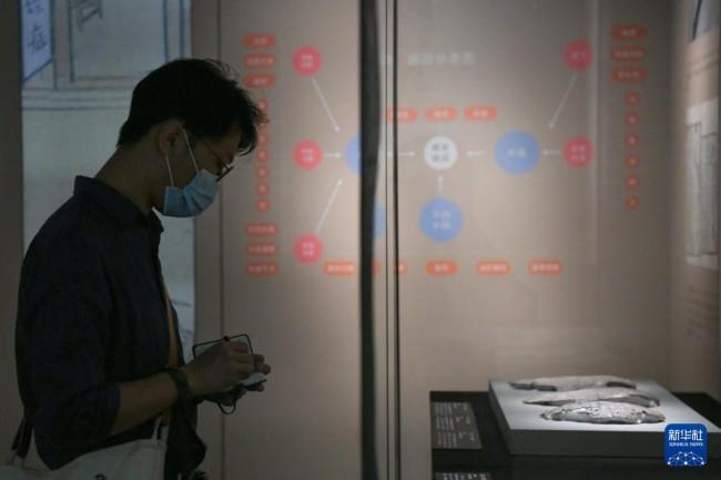 """9月17日,市民在""""发现中医之美——中国传统医药文物特展""""上做记录。新华社记者 胥冰洁 摄"""