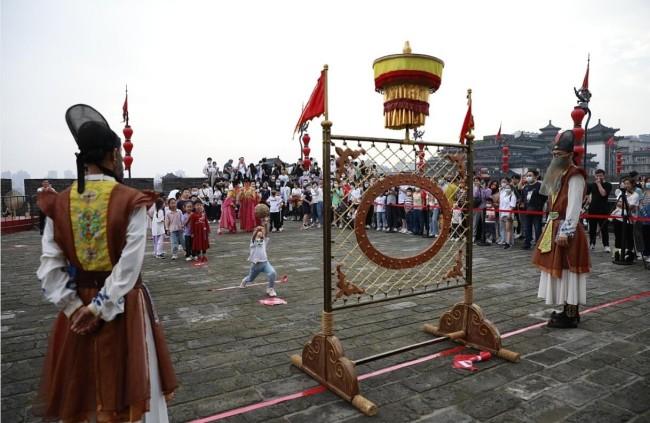 """西安城墙上举办""""大唐运动会"""" 游客体验蹴鞠游戏"""