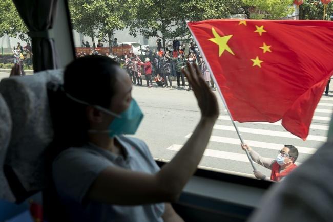 4月15日,武汉市民挥舞国旗,送别北京协和医院国家援鄂抗疫医疗队。新华社记者 熊琦 摄