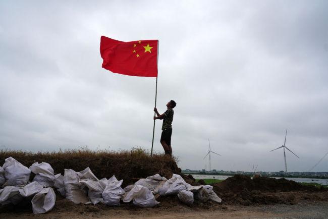 7月16日,在江西省九江市,退役军人张恒扶正防洪哨所门前的国旗。洪水来袭,曾服役于天安门国旗护卫队的张恒同父亲一起投身防汛抗洪战斗。他说,过去我护卫的是国家的荣誉和尊严,现在我守卫的是父母和家乡。新华社记者 周密 摄