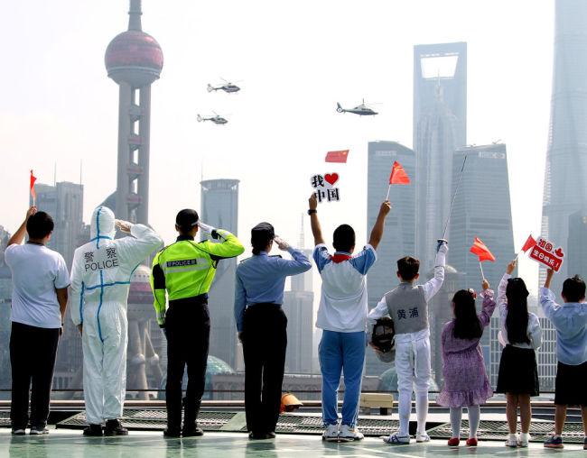 10月1日,警用直升机悬挂着五星红旗飞过上海黄浦江上空。新华社记者 陈飞 摄