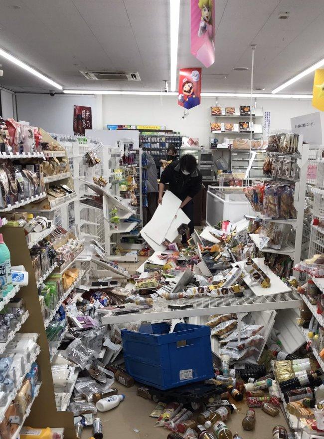 福岛市一家便利店店员正在收拾地震后散落一地的货物。图源:社交媒体