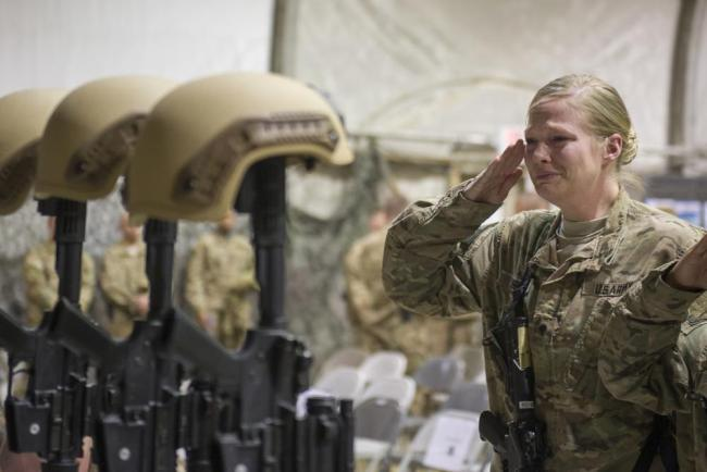 △2015年12月23日,一名美军士兵在美军驻阿富汗的巴格拉姆空军基地向死于自杀式袭击的6名战友表达敬意(图片来源:美联社)