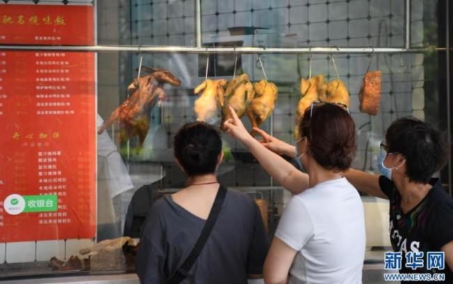 5月30日,市民在广钢新城一小区门店选购烧味。 新华社记者 邓华 摄