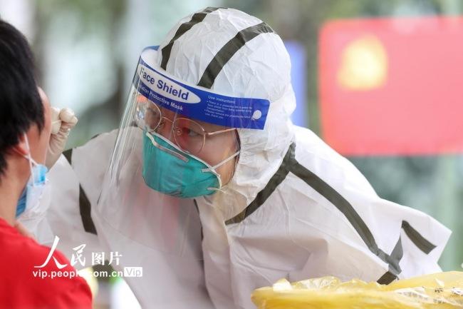 8月9日拍摄于扬州邗江区邗江中学检测点,医护人员正在为居民进行核酸采样。