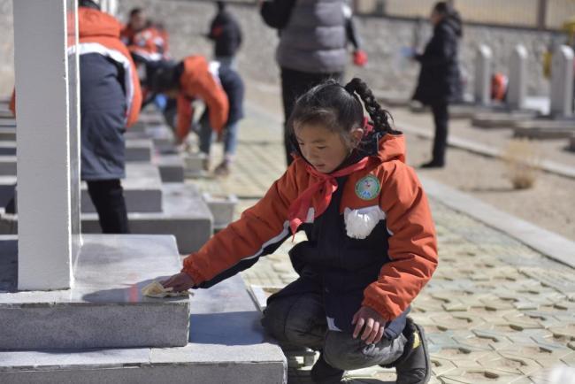 小学生细心擦拭着烈士的墓碑。(2021年4月4日 新华社记者翟永冠 摄)