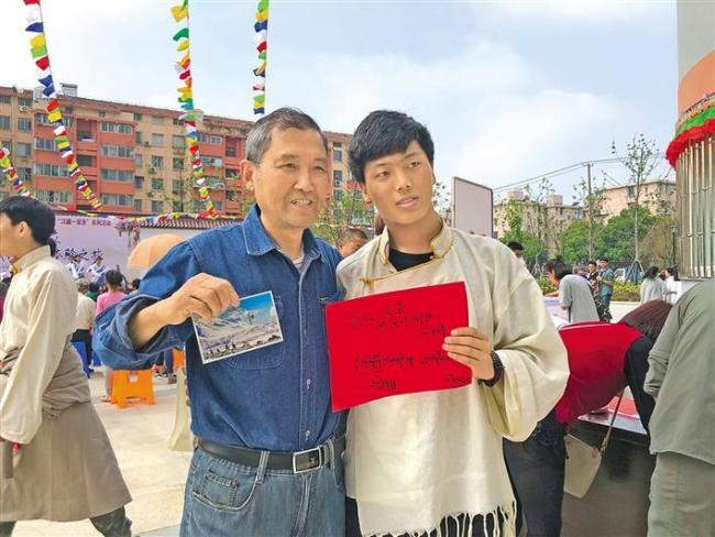 图为江苏省南通中学藏文化社团在南通市北濠社区开展藏文化宣传与展示活动时,藏族学生把藏文书写的明信片赠送给当地市民。图片由江苏省南通中学提供
